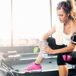 Young woman holding water bottle in gym
